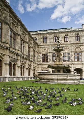 Beautiful garden in the Opera House of Vienna, Austria, with some pigeons on the grass - stock photo