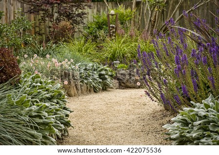 Beautiful garden pathway, flanked by lush thick floliage, fence in background - stock photo