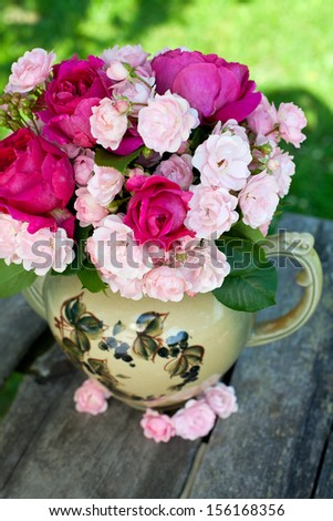 beautiful garden roses in a tea pot isolated on white - stock photo