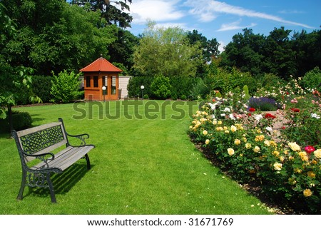 Beautiful garden with blooming roses, brick path, bench and a small gazebo - stock photo