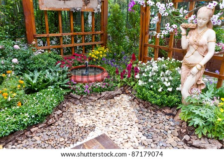 beautiful garden with small fountain - stock photo