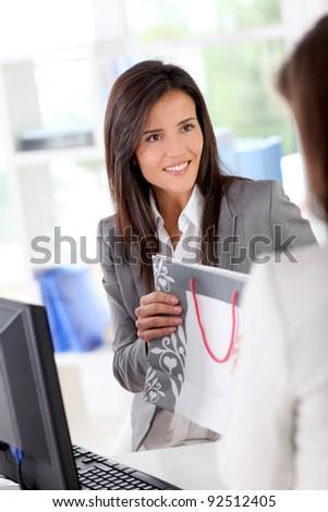 Beautiful garment store seller talking to customer - stock photo