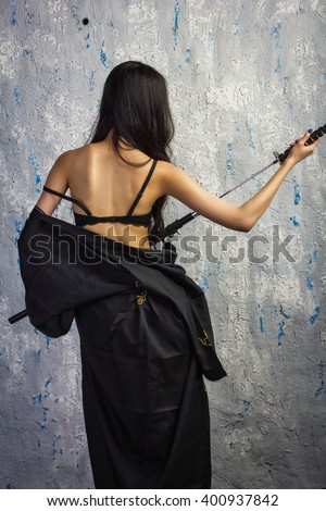 Beautiful geisha in kimono with samurai sword - stock photo