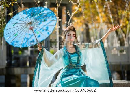 beautiful geisha with blue umbrella on stone bench - stock photo