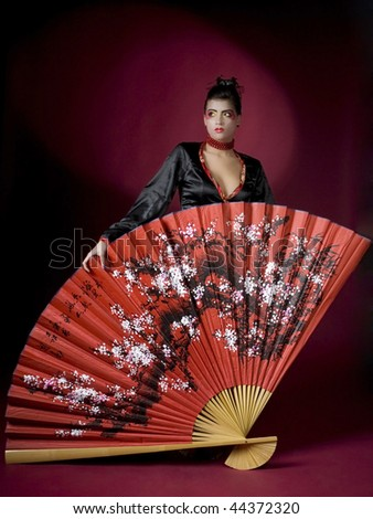 Beautiful geisha with huge painted fan, studio shot - stock photo