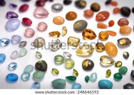 Beautiful gems background. Many real colorful gemstones: citrine, amethyst, topaz, ruby, emerald, prehnite, rose quartz, moonstones, tiger eye, labradorite, peridot and many more. - stock photo