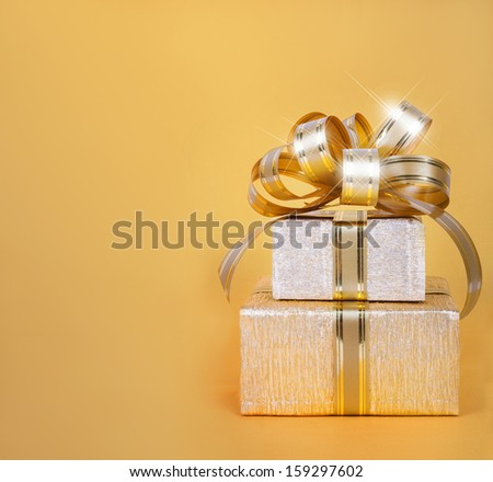 Beautiful  Gift box in gold wrapping paper on abstract background - stock photo