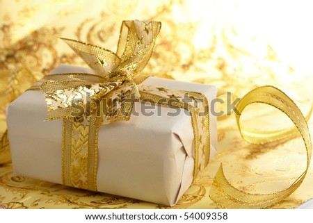 Beautiful gift box on the gold background - stock photo