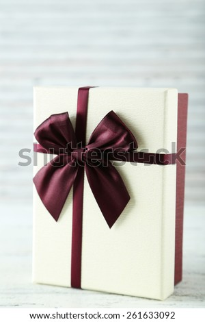 Beautiful gift box on white wooden background - stock photo