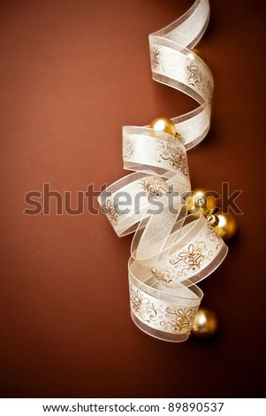 Beautiful gift ribbon and christmas balls on brown background - stock photo