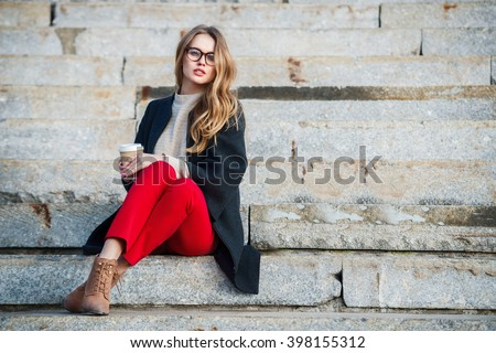 Beautiful gil with coffee cup sitting on outdoors stairs wearing red pants and glasses. - stock photo