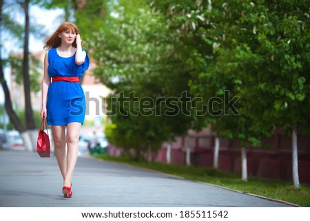 Beautiful ginger-haired woman in blue dress outdoors