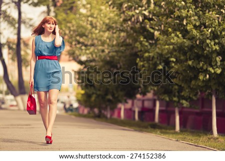 Beautiful ginger-haired woman in blue dress outdoors - stock photo