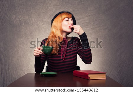 beautiful ginger lady eating a cookie and drinking tea or coffee on grunge background - stock photo