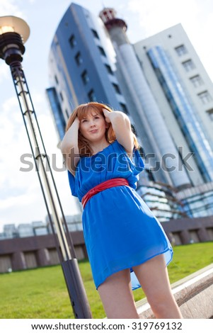 Beautiful ginger woman in blue dress and red belt against building - stock photo