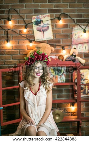 Beautiful girl acrobat, magician's assistant, sitting behind the scenes of the circus arena among the props for the repose