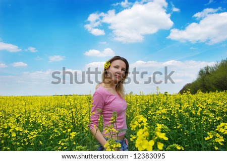 Beautiful girl among blooming rapeseed oilseed field