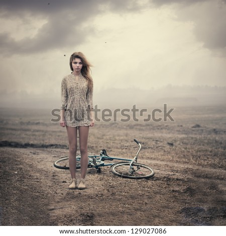 beautiful girl and a bike in the countryside on a cloudy day - stock photo
