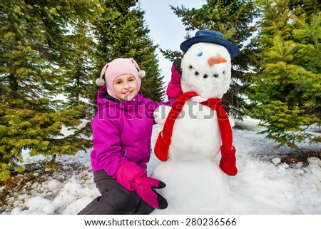 Beautiful girl and cute snowman with red scarf - stock photo