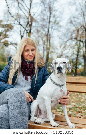 Beautiful girl and dog sitting on the wooden bench
