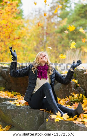Beautiful girl and falling leaves, autumn color - stock photo