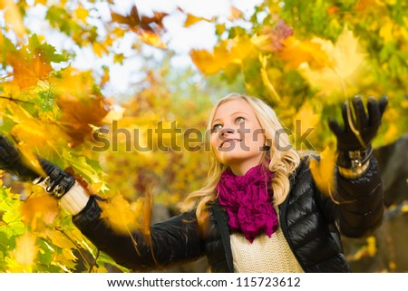 Beautiful girl and falling leaves, autumn color, horizon format - stock photo