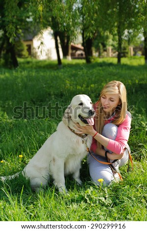 Beautiful girl and golden retriever sitting nearby. Girl petting dog