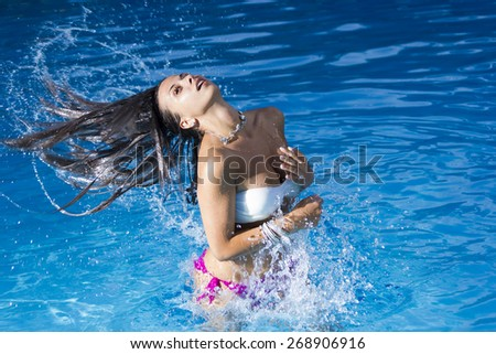 Beautiful girl and water splashes in the swimming pool.