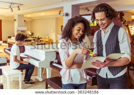 Beautiful girl and young man reading and smiling, standing in a musical shop. In the background young Afro-American man playing a piano - stock photo
