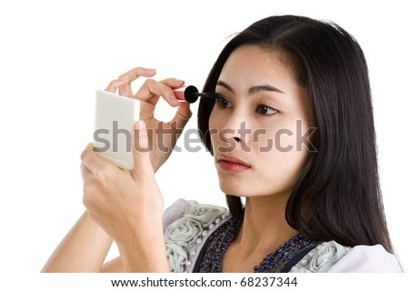 beautiful girl applying black mascara on her eyes, isolated on white background