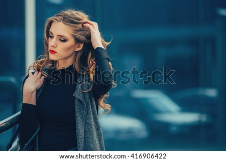 Beautiful girl at the business center in the open air. There are a lot of cases. - stock photo