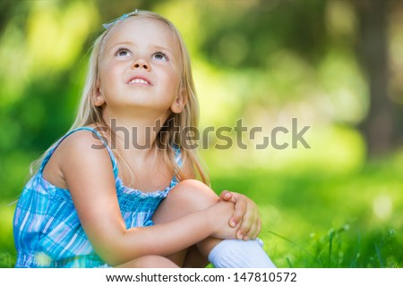 Beautiful girl at the park daydreaming and looking very happy - stock photo