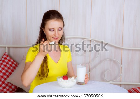 beautiful girl at the table eating cheese and drinking milk - stock photo