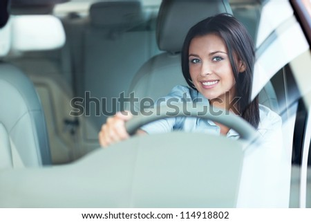 Beautiful girl at the wheel a car - stock photo