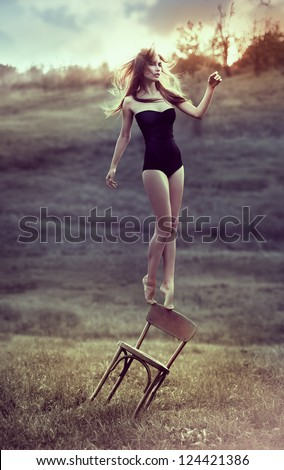beautiful girl balances on back of chair outdoors. Artwork - stock photo