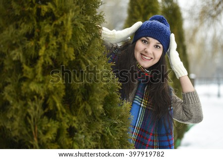 Beautiful girl behind the tree and laughs
