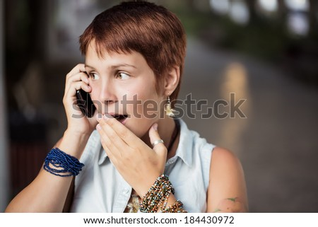 Beautiful girl being surprised by a call - stock photo