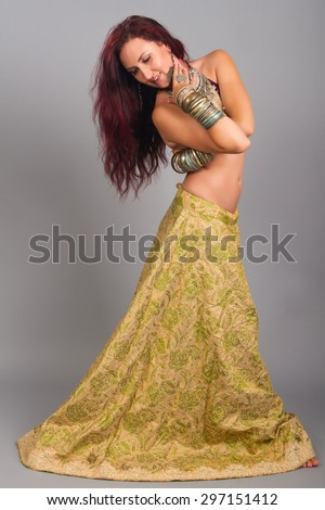 Beautiful girl belly dance movement, Young beautiful belly dancer in a  golden costume