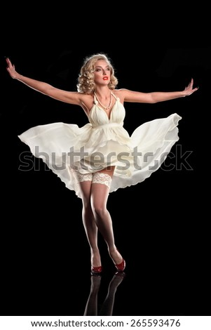 beautiful girl blonde in white dress. studio photography, on a black background. dress fluttering in the wind. hair and makeup style pin-up - stock photo