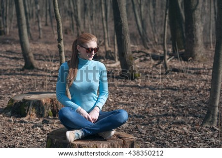 beautiful girl blonde sits in lotus pose in the middle of the forest in the spring - stock photo