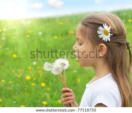 Beautiful girl blowing dandelions - stock photo