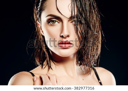 beautiful girl brunette model with wet hair on a black background