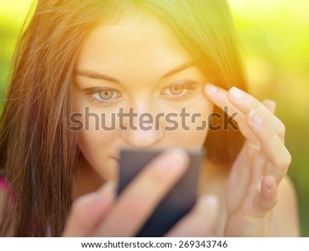 Beautiful girl checking her makeup outdoor - stock photo