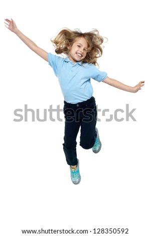 Beautiful girl child jumping high in air, arms outstretched sideways. - stock photo