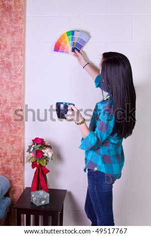 Beautiful Girl Choosing a Color to Paint the Wall - stock photo