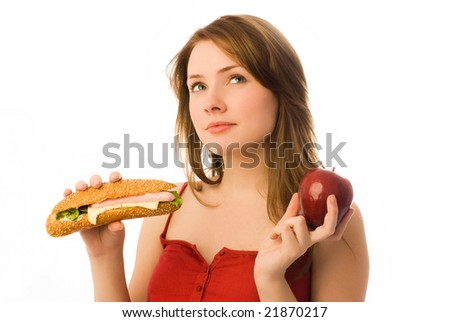 beautiful girl choosing between an apple and hot dog isolated against white background - stock photo