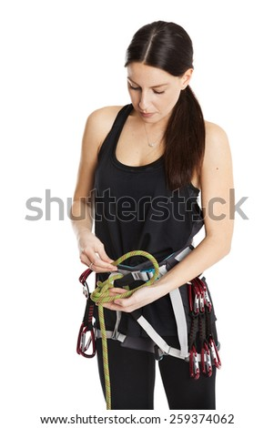 Beautiful girl climber explain how to make the safety knot before climb. Fully equipped for rock climbing, extreme sport. Isolated on white background. - stock photo