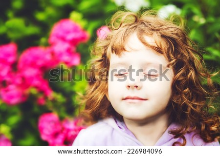 Beautiful girl closed her eyes and breathes the fresh air in the park. - stock photo