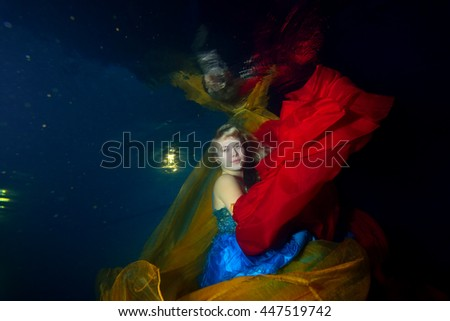 Beautiful girl dancing underwater with red and orange cloth in blue dress on a black background. Portrait. Horizontal orientation. - stock photo