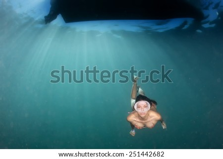 beautiful girl diving in the deep blue sea